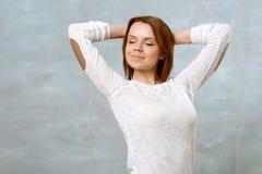 Jeune femme se tenant avec des bras derrière sa tête photo libre de droits