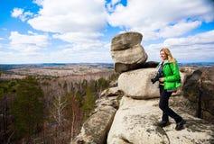 Jeune femme se tenant avec l'appareil-photo sur le bord du ` s de falaise Photographie stock