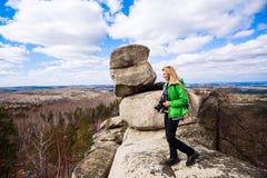 Jeune femme se tenant avec l'appareil-photo sur le bord du ` s de falaise Image libre de droits