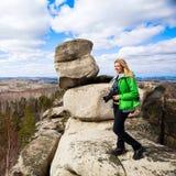 Jeune femme se tenant avec l'appareil-photo sur le bord du ` s de falaise Photographie stock libre de droits