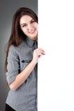 Jeune femme se tenant avec le panneau d'affichage d'isolement Photographie stock libre de droits