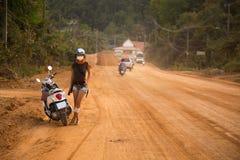 Jeune femme se tenant à côté d'une motocyclette Photo stock