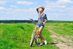 Jeune femme se tenant à côté de son vélo Photos stock