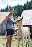 Jeune femme se tenant choyante un poulain Photo stock