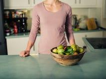 Jeune femme se tenant dans la cuisine avec le bol de pommes images stock