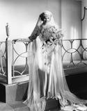 Jeune femme se tenant dans la robe et la participation de mariage un bouquet des fleurs (toutes les personnes représentées ne son Photographie stock libre de droits