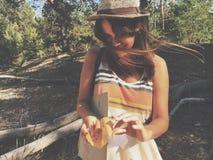 Jeune femme se tenant dans la robe supérieure avec le chapeau occidental dans l'herbe grande devant une forêt images libres de droits