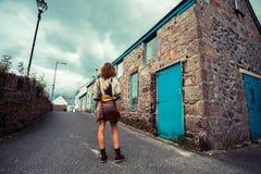 Jeune femme se tenant dans la rue en dehors de la vieille maison Images stock