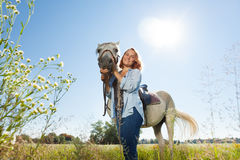 Jeune femme se tenant dans le domaine avec son cheval blanc Image libre de droits