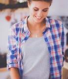 Jeune femme se tenant dans sa cuisine Photographie stock libre de droits