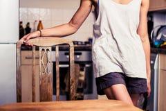 Jeune femme se tenant dans sa cuisine photographie stock