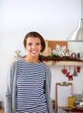 Jeune femme se tenant dans sa cuisine près du bureau Photos stock
