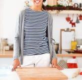 Jeune femme se tenant dans sa cuisine près du bureau Images stock