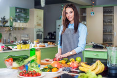 Jeune femme se tenant dans sa cuisson de port de tablier de cuisine, coupant le fruit sur un conseil Photos stock
