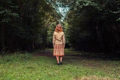 Jeune femme se tenant dans un dédouanement de la forêt Images stock