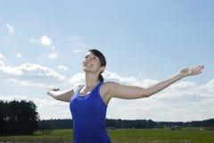 Jeune femme se tenant dehors avec ses bras grands ouverts Images stock