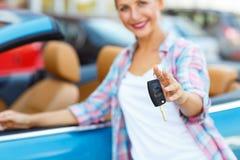 Jeune femme se tenant près d'un convertible avec des clés à disposition Photo stock