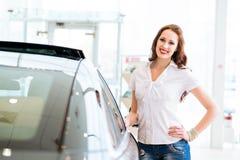 Jeune femme se tenant près d'une voiture Photo stock