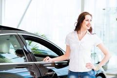 Jeune femme se tenant près d'une voiture Photos stock