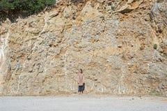 Jeune femme se tenant près de la pente de montagne Image libre de droits