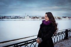Jeune femme se tenant près de la rivière neigeuse sur la promenade de ville Photographie stock libre de droits