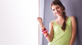 Jeune femme se tenant près du mur foncé Photographie stock libre de droits