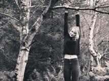 Jeune femme se tenant sur l'arbre photo stock