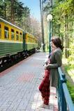 Jeune femme se tenant sur la gare ferroviaire Photographie stock libre de droits