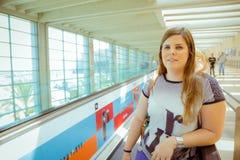 Jeune femme se tenant sur la ligne d'escalator dans le terminal d'aéroport et le l Image stock