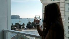 Jeune femme se tenant sur le balcon et l'eau potable dehors banque de vidéos