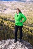 Jeune femme se tenant sur le bord du ` s de falaise Photographie stock libre de droits