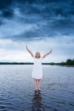Jeune femme se tenant sur un lac avec une tempête puissante derrière elle Photos stock