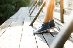 Jeune femme se tenant sur un pont dans des espadrilles de jeans Images libres de droits