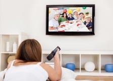 Jeune femme se trouvant à son lit et télévision de observation Image stock