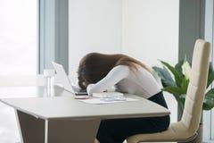 Jeune femme se trouvant au bureau devant l'ordinateur portable photographie stock libre de droits