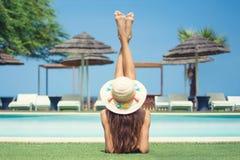 Jeune femme se trouvant par la piscine appréciant le bronzage image stock