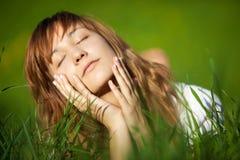 Jeune femme se trouvant sur l'herbe Images stock
