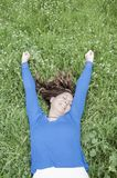 Jeune femme se trouvant sur l'herbe au printemps photographie stock libre de droits