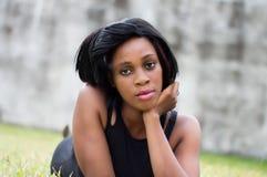 Jeune femme se trouvant sur la pelouse photographie stock libre de droits