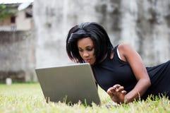 Jeune femme se trouvant sur la pelouse avec l'ordinateur portable photo stock