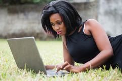 Jeune femme se trouvant sur la pelouse avec l'ordinateur portable image libre de droits