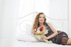 Jeune femme se trouvant sur le lit avec le bouquet de fleur Photo libre de droits