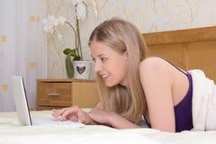 Jeune femme se trouvant sur le lit dans la chambre à coucher et à l'aide de l'ordinateur portable Image libre de droits