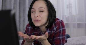 Jeune femme se trouvant sur le lit et ayant la causerie visuelle utilisant le webcam sur l'ordinateur portable clips vidéos