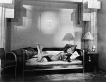 Jeune femme se trouvant sur un divan et lisant un magazine (toutes les personnes représentées ne sont pas plus long vivantes et a photo stock