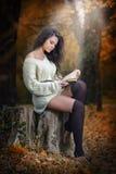 Jeune femme sensuelle caucasienne lisant un livre dans un paysage romantique d'automne. Portrait de fille assez jeune dans la forê Image libre de droits
