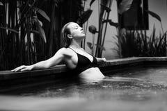 Jeune femme sensuelle détendant dans la piscine extérieure d'infini de station thermale entourée avec la verdure tropicale luxuri images libres de droits