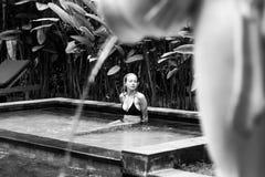Jeune femme sensuelle détendant dans la piscine extérieure d'infini de station thermale entourée avec la verdure tropicale luxuri photos stock