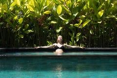 Jeune femme sensuelle d?tendant dans la piscine ext?rieure d'infini de station thermale entour?e avec la verdure tropicale luxuri photographie stock