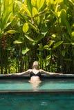 Jeune femme sensuelle d?tendant dans la piscine ext?rieure d'infini de station thermale entour?e avec la verdure tropicale luxuri image libre de droits